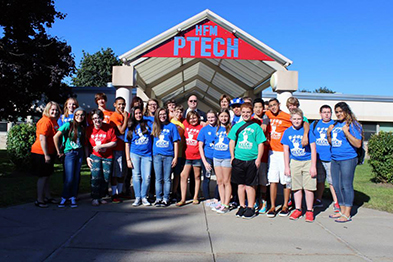 P-TECH students posing in front of their school's entrance.