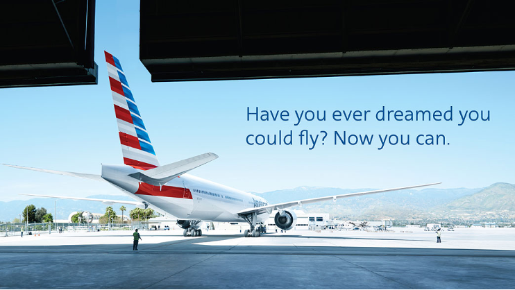 An American Airlines jet leaving the hangar. Words on the image read: Have you ever dreamed you could fly? Now you can.