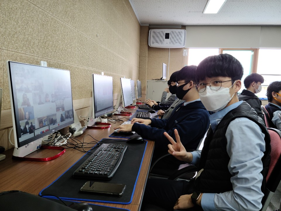 P-TECH student wearing face mask and showing a peace sign with his hand in front of a computer